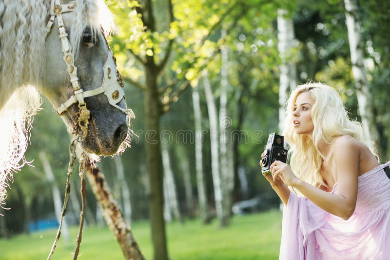 Beautiful woman taking pictures of the horse royalty free stock images