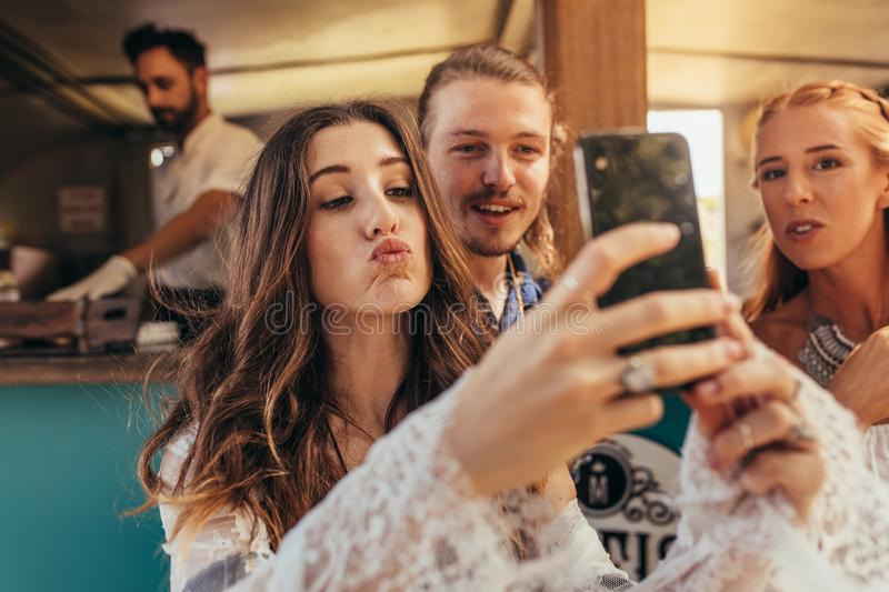 Beautiful woman taking selfie with friends royalty free stock photos
