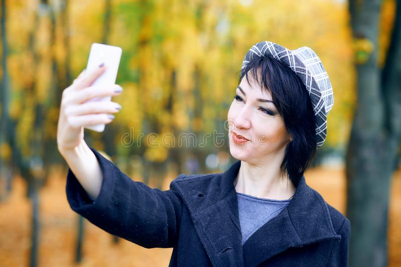 Beautiful woman taking selfie by smartphone and having fun in autumn city park, fall season, yellow leaves royalty free stock images