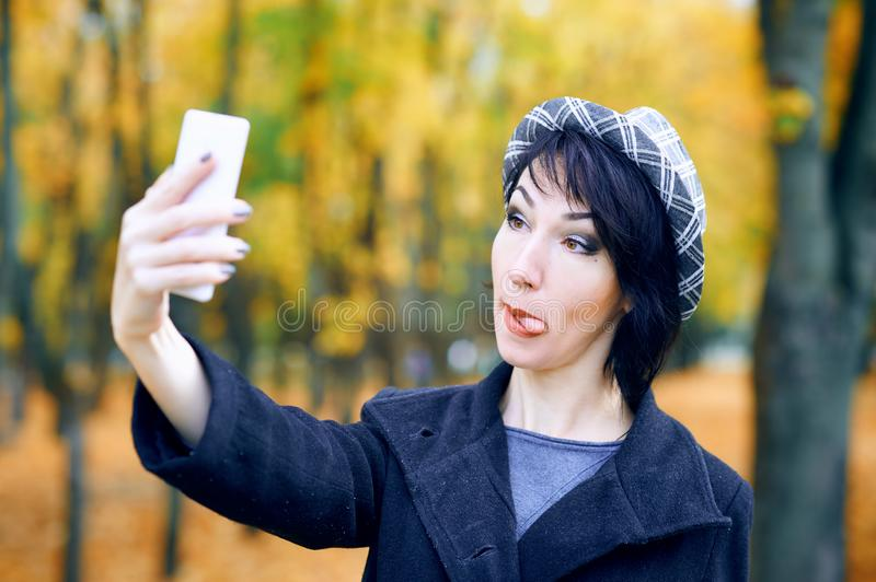 Beautiful woman taking selfie by smartphone and having fun in autumn city park, fall season, yellow leaves stock images
