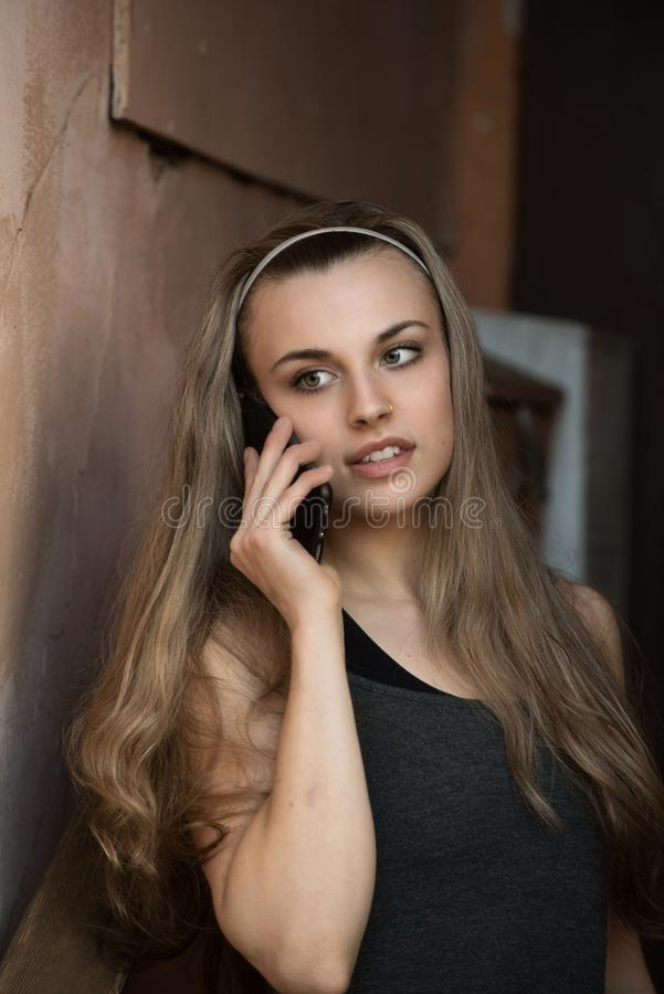 Art portrait of a beautiful girl. gorgeous blonde girl, portrait talking on a cell phone stock photography