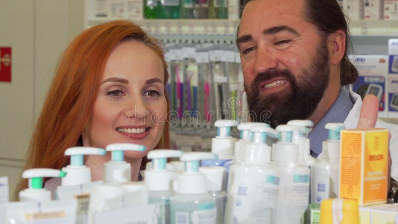 Beautiful woman talking to the pharmacist, while selecting products to buy stock photos