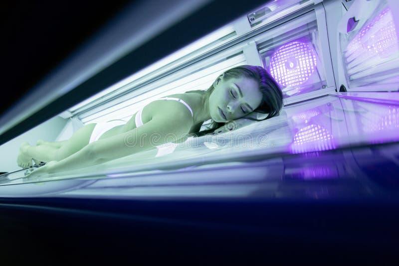 Beautiful woman tanning in solarium stock images