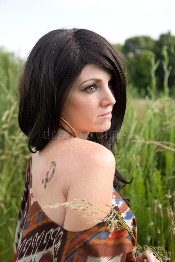 Beautiful Woman With Tattoo. A portrait of a woman out in a field with a tattoo of moon and stars on her back stock image