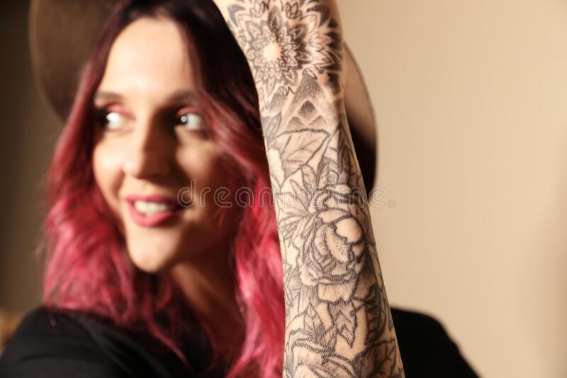 Beautiful woman with tattoos on arm against background, focus on hand. Beautiful woman with tattoos on arm against beige background, focus on hand royalty free stock images