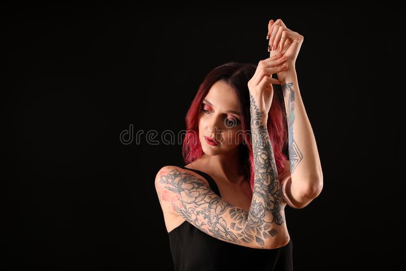 Beautiful woman with tattoos on arms against background. Space for text. Beautiful woman with tattoos on arms against black background. Space for text stock photos
