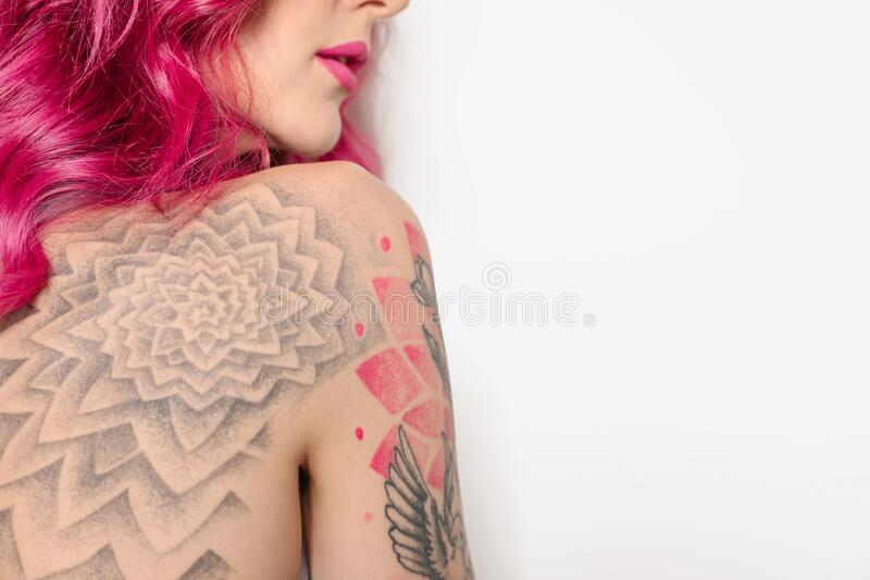 Beautiful woman with tattoos on body against background, closeup. Space for text. Beautiful woman with tattoos on body against white background, closeup. Space stock image
