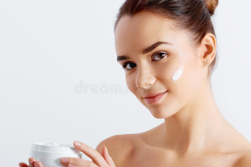 Beautiful woman tender jar of moisturizer cream. Close-up fresh young woman face. isolated on white stock images