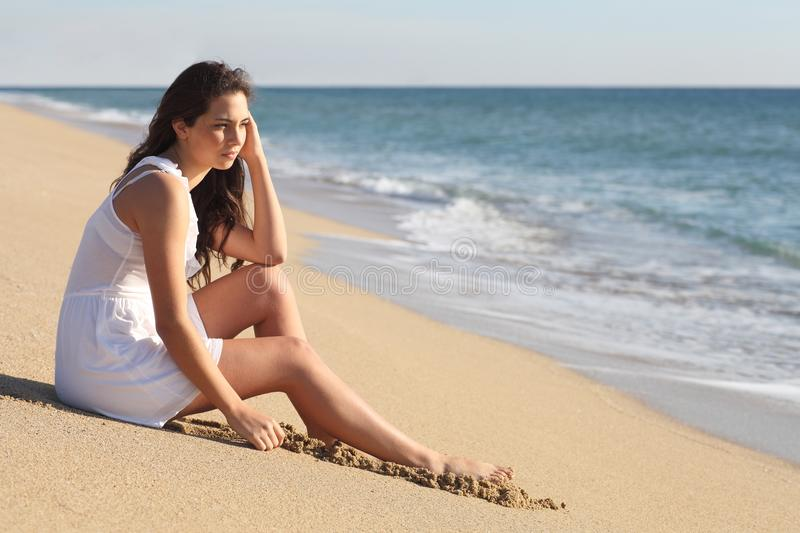 Beautiful woman thinking and watching the sea stock photography