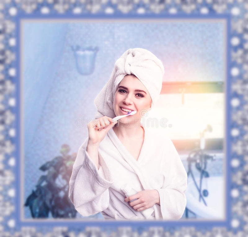 Beautiful woman with toothbrush brushing her teeth stock photo