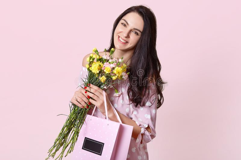 Beautiful woman with toothy smile, has long dark straight hair, tilts head, carries bouquet of flowers and bag with present, poses royalty free stock photos