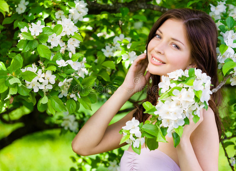 Beautiful woman touches face near the flowered tree royalty free stock photo
