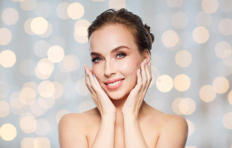 Beautiful woman touching face over holidays lights. Beauty, people and health concept - beautiful young woman touching her face over holidays lights background stock images
