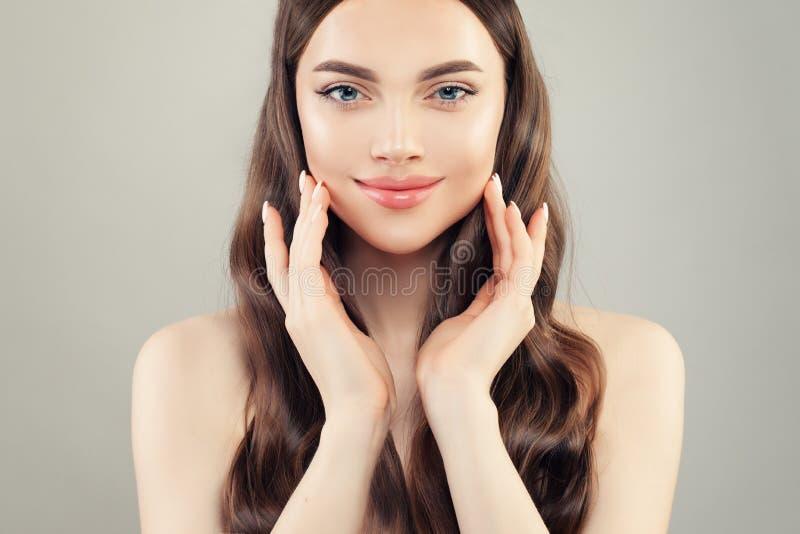Beautiful woman touching her hand her cheeks. Pretty face closeup.  stock photos