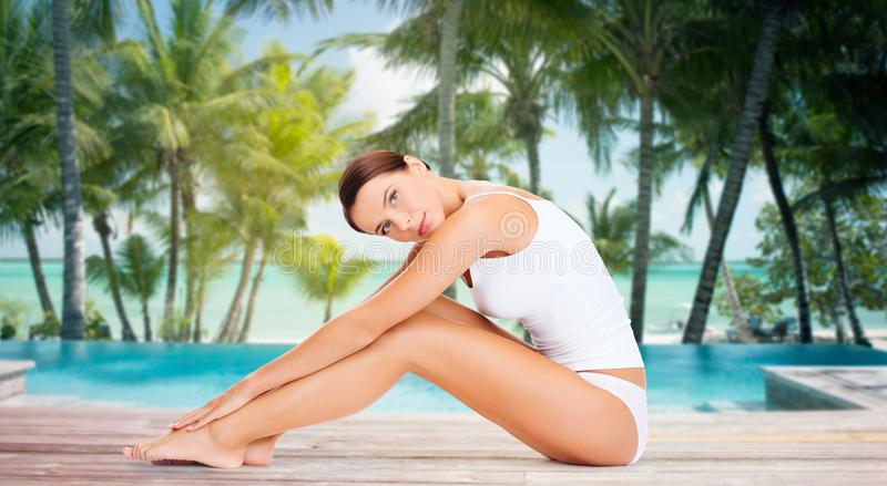Beautiful woman touching her legs over beach royalty free stock photo