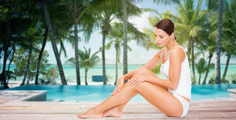 Beautiful woman touching her legs over beach royalty free stock photos