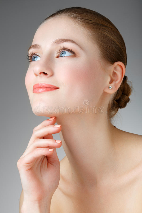 Beautiful Woman Touching her neck. Smiling girl with blue eyes. stock image
