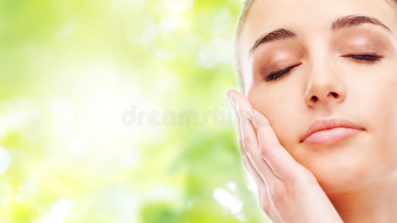 Beautiful woman touching her smooth skin. Beautiful young woman touching her radiant face skin with eyes closed on green background stock photos