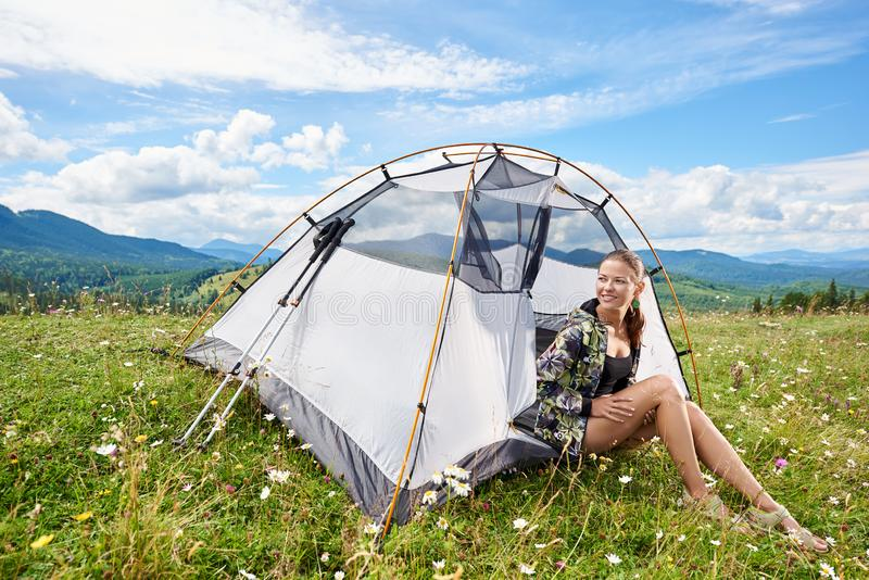 Woman tourist hiking in mountain trail, enjoying summer sunny morning in mountains near tent royalty free stock photo
