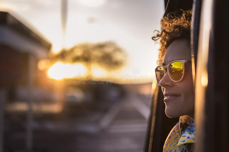 Beautiful woman travel on a car looking outside and enjoy the light of the golden sunset on her face. nice lifestyle and peaceful stock photo