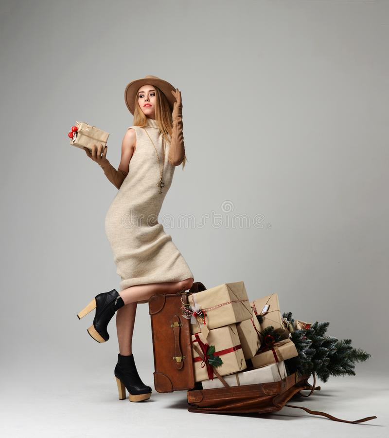 Beautiful woman traveler in hat with big open leather retro bag full of christmas present gifts. Looking at the corner on grey background. New year concept stock photo