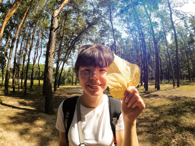 Beautiful woman traveling with backpack and tent, smiling with yellow  leaf in forest stock image