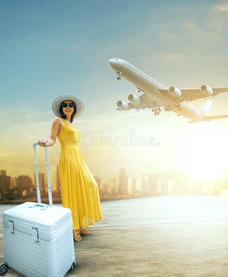 Beautiful woman and traveling luggage standing in airport terminal with passenger plane flying over sky. Beautiful woman and traveling  luggage standing in stock image