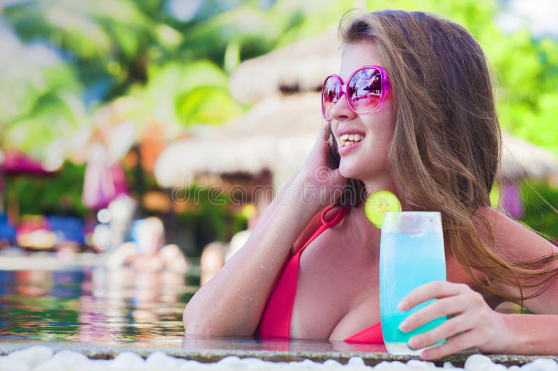 Beautiful woman with tropical cocktail in the pool royalty free stock image