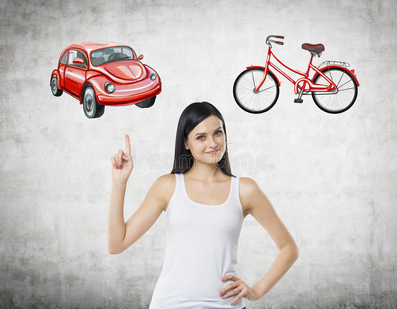 A beautiful woman is trying to chose the most suitable way for travelling or commuting. Her choice is a car. Two sketches of a car. And a bicycle are drawn on royalty free stock image