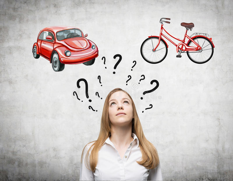 A beautiful woman is trying to chose the most suitable way for travelling or commuting. Two sketches of a car and a bicycle are dr. Awn on the concrete wall royalty free stock photos