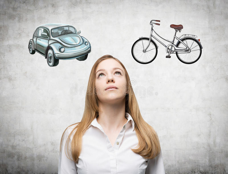 A beautiful woman is trying to chose the most suitable way for travelling or commuting. Two sketches of a car and a bicycle are dr. Awn on the concrete wall royalty free stock photography