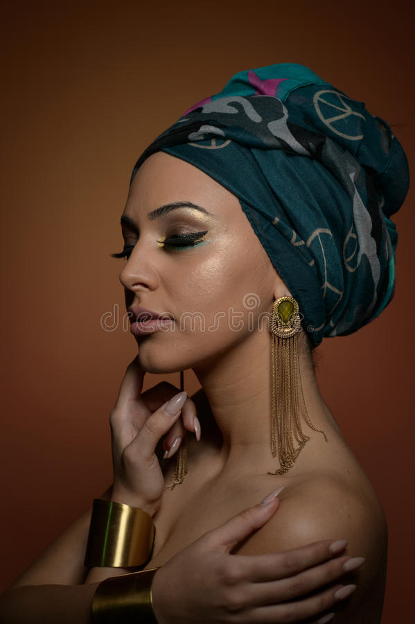 Beautiful woman with turban. Young attractive female with turban and golden accessories. Beauty fashionable woman stock images