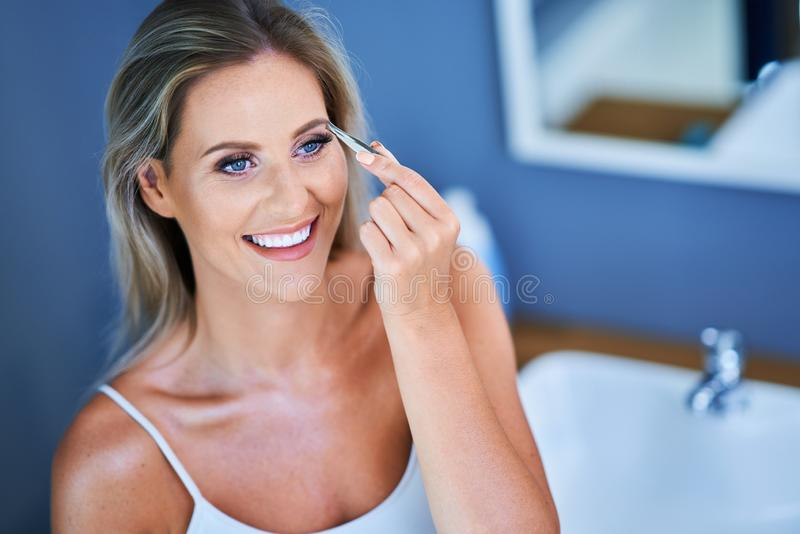 Beautiful woman with tweezers in the bathroom. Picture of adult woman in the bathroom royalty free stock image