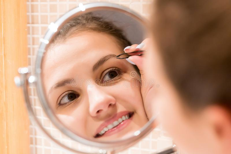 Beautiful woman with tweezers is plucking eyebrows while looking into the mirror in bathroom. Beauty skincare and wellness morning. Concept stock image
