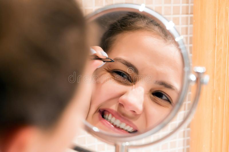 Beautiful woman with tweezers is plucking eyebrows while looking into the mirror in bathroom. Beauty skincare and wellness morning. Concept royalty free stock image