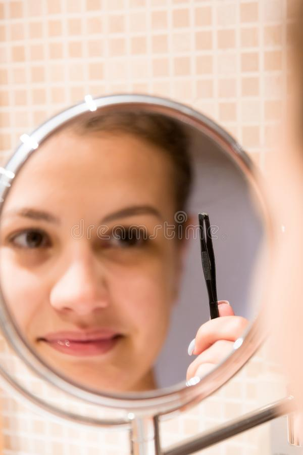 Beautiful woman with tweezers is plucking eyebrows while looking into the mirror in bathroom. Beauty skincare and wellness morning. Concept royalty free stock photography