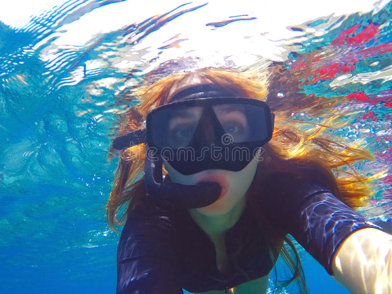 Beautiful woman under water before dive to coral reef stock image
