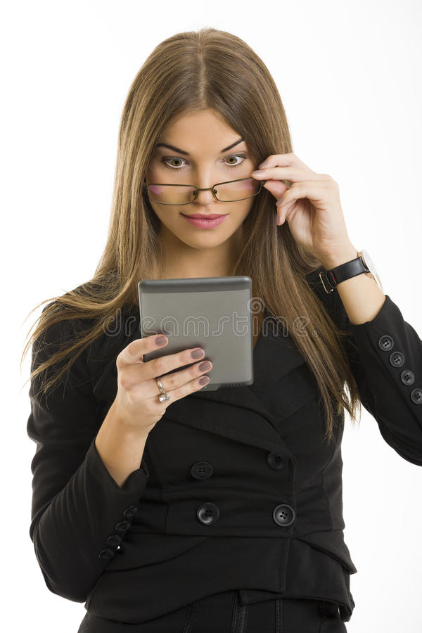 Beautiful woman using ebook reader. Beautiful surprised long-haired young woman looking over her eyeglasses at her e-book reader display over white background royalty free stock photos