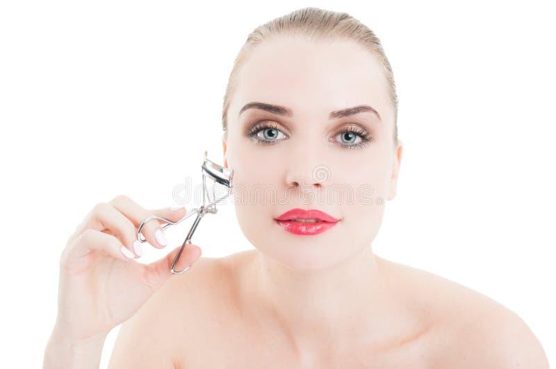 Beautiful woman using eyelash curler royalty free stock photography