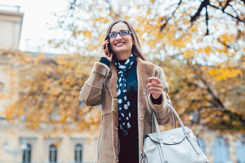 Beautiful woman using her phone in the city in autumn stock image