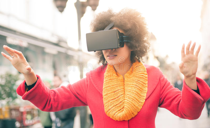 Beautiful woman using high tech virtual reality glasses outdoor stock image