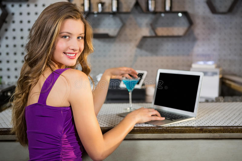 Beautiful woman using laptop while having cocktail stock photography