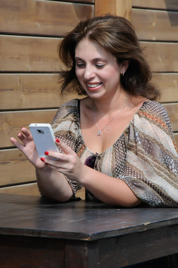 Beautiful woman is using a smartphone stock image