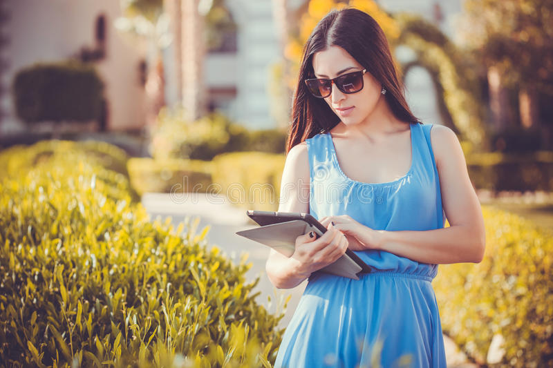 Beautiful woman using tablet in green park royalty free stock photography