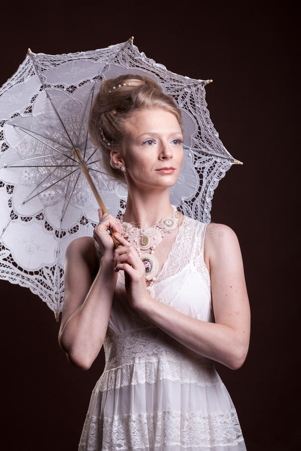 Beautiful woman in victorian style holding a lace umbrella. Luxury and elegance royalty free stock image