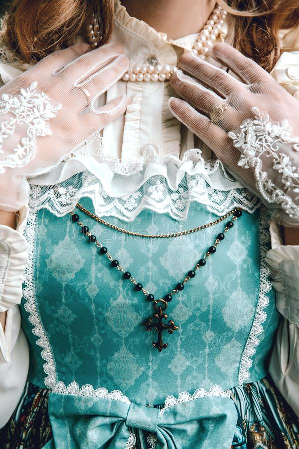 Beautiful rich woman in vintage blue dress. Cross. Victorian lady. Elegant royalty free stock photography