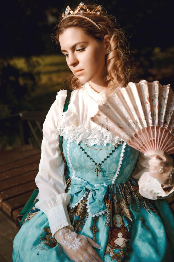 Beautiful rich woman in vintage blue dress with fan in crown diadem. Victorian lady. Elegant royalty free stock photography