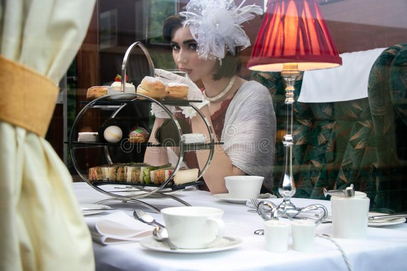 Beautiful woman in vintage clothing enjoying afternoon tea in train carriage royalty free stock images