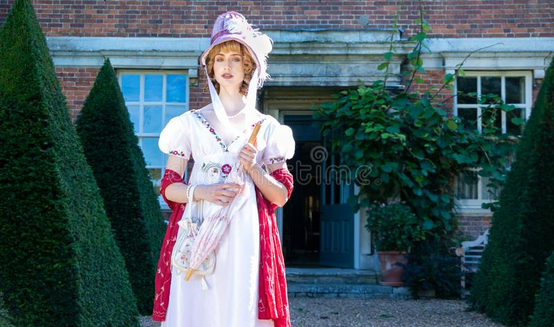 Beautiful woman in vintage Georgian dress and bonnet standing in garden of stately home. Beautiful lady wearing vintage regency dress and bonnet, carrying a royalty free stock photo