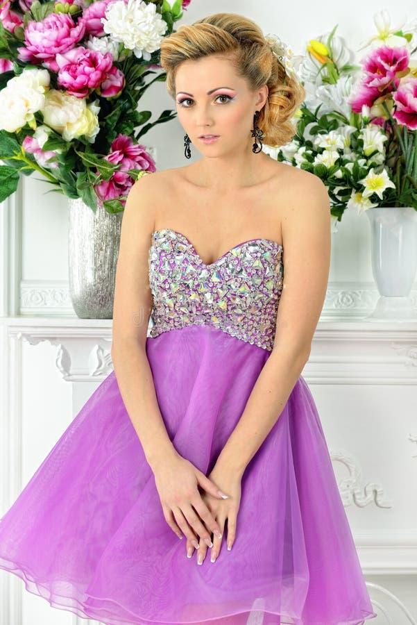 Beautiful woman in violet dress in luxury studio. royalty free stock image